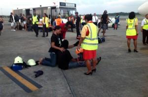 Passagiers op de landingsbaan van Zanderij na de voorzorgslanding van DAE