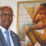 Justitie Minister Dennis Richardson poseert in zijn kantoor bij een schilderij van een van zijn favoriete lokale kunstenaars - Ras Mosera - foto Today / Hilbert Haar