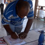 Een bezoeker zet zijn handtekening onder de petitie (foto: Elisa Koek)