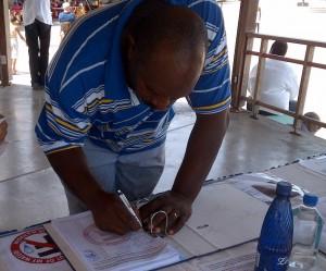 Een man zet zijn handtekening onder de petitie (foto: Elisa Koek)