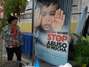 Gezaghebber Lydia Emerencia kijkt naar de poster met de tekst Stop Kindermishandeling - Foto: Belkis Osepa