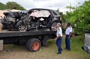 Politie agenten inspecteren de totaal vernielde auto van Curtis Heyliger. Foto Today / Leo Brown