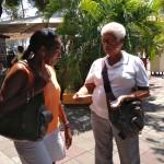 Vrijwilligster Glenda deelt een folder van het hospice uit - foto: Anneke Polak