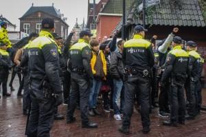 Een groep opgepakte demonstranten worden door een barricade van politie richting een bus afgevoerd.