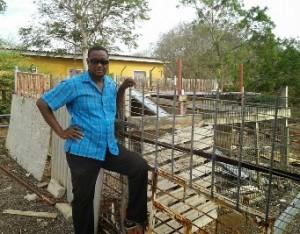Luthson Rosina poseert voor zijn lege geitenhok (foto Elisa Koek)
