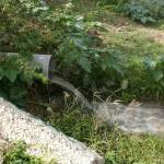 Pijp met stromend rioolwater bij Tera Kora - foto: Michelle da Costa Gomez