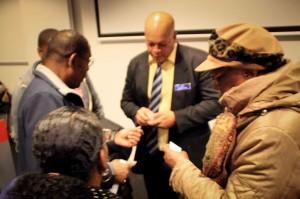 FKP-directeur Arthur Con in gesprek met Curaçaoënaars in Amsterdam vlak na een presentatie over volkshuisvesting op Curaçao.- foto: John Samson