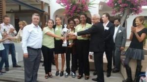Minister President Marcel Gumbs reikt de trofee uit aan het winnende team. Links staat coach Roy Moes. Foto Today / Hilbert Haar