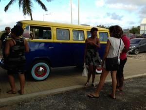 Een busje met het opschrift 'geslaagd' komt aangereden bij de school. Michelle Gumbs staat te praten met medeleerlingen - foto: Janita Monna