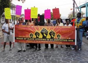 Deelnemers aan de Mars voor Autonomie houden protestborden omhoog– foto: The Daily Herald/Althea Merkman