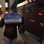 Een vrouw houdt de Arubaanse vlag stevig vast tijdens de protestacties in Den Haag, terwijl de Mobiele Eenheid klaar staat om de mensen uit straten te vegen. - foto: John Samson