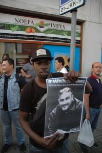 Een demonstrant toont een portret van Mitch Henriquez - foto: Pieter Hofmann.