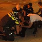 Vrienden en agenten ontfermen zich over een gewonde man tijdens rellen in de Schilderswijk. Foto: Pieter Hofmann.