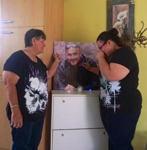 Moeder Maria en zus Jermaine bij een uitvergrote foto van Mitch - foto: Sharina Henriquez