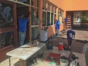 Reparaties aan onder meer de voordeur van het Arubaanse parlement op de dag na de rellen. Foto: Ariën Rasmijn