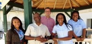 Photo: Saba Educational Foundation (SEF) voorzitter Franklyn Wilson, Saba Comprehensive School Directeur en SEF Secretaris/Vice-Directeur La-Toya Charles samen met twee studenten om een photo te maken op het school.