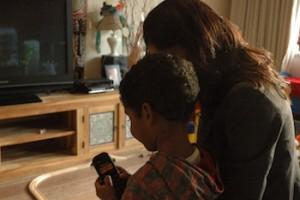 Persaud herhaalt voor haar zoon een telefoonnummer in het Papiaments. Foto: Pieter Hofmann.