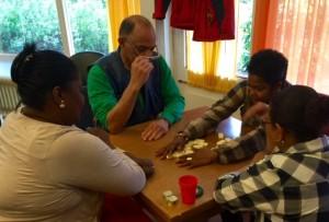 Bewoners en vrijwilligers spelen domino bij de dagopvang voor ouderen in Rotterdam-Zuid. Foto: Pieter Hofmann.