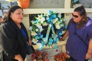 Oudste zus Lila en jongste zus Sherry leggen een krans bij het graf van hun broer Mitch Henriquez - foto: Sharina Henriquez