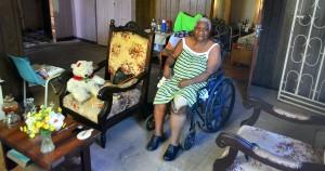 Catherine Mitchel in haar woonkamer. Met rolstoel en prothese | foto: Dick Drayer