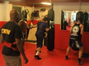 Josemir Poulino traint op de bokszak onder toezicht van coach Raymond Joval (links). Foto: Pieter Hofmann.