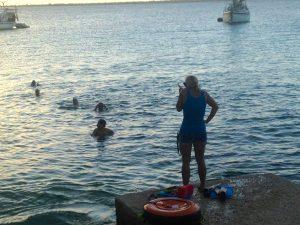 In het tegenlicht van de ondergaande zon heeft trainster Anita Smits moeite de zwemmers te onderscheiden - foto: Gijs van den Heuvel